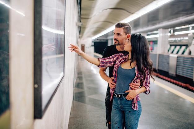 Jeune homme et femme utilisent le métro. couple dans le métro. gens occasionnels dans la métropole. jeune femme pointe sur mur et sourire. guy tient la main sur ses hanches.