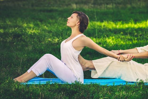 Jeune homme et femme vêtus d'une robe blanche faisant un massage thaï avec des exercices de yoga assis sur le