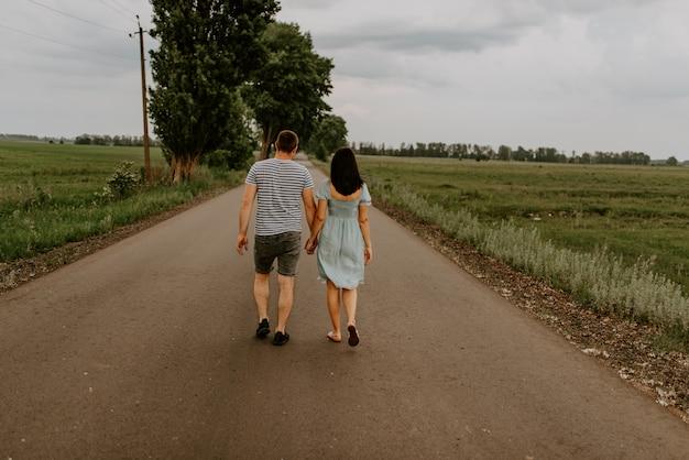 Jeune homme et femme vont main dans la main le long de la route.