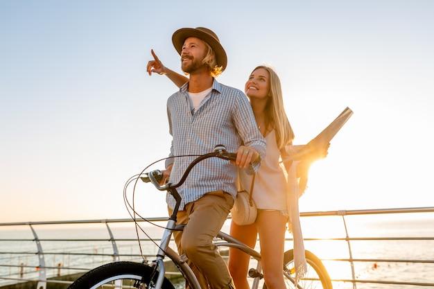 Jeune homme et femme voyageant sur des vélos tenant une carte