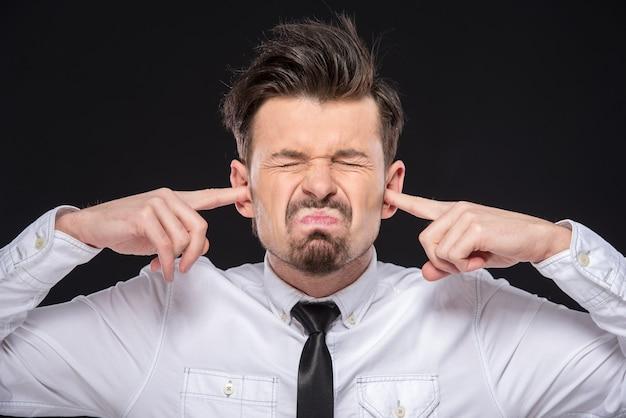 Jeune homme ferme ses oreilles car trop fort.