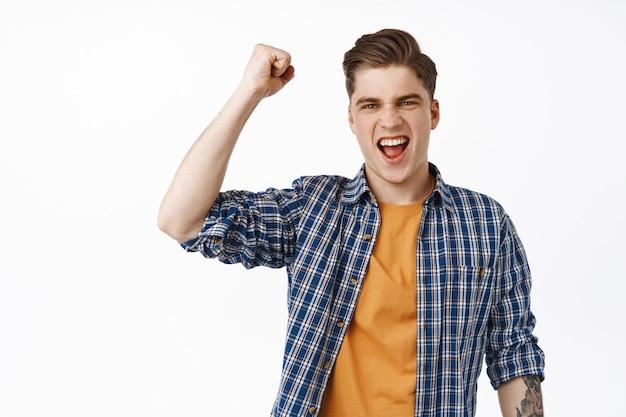 Jeune homme féroce et excité chantant, pompe à poing et criant, regardant la compétition, fan de jeux de sport regardant la télévision, criant de joie, célébrant, debout sur blanc