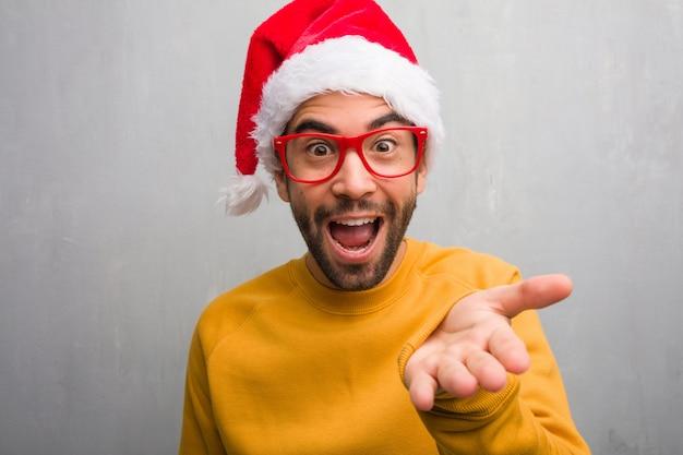 Jeune homme fête le jour de noël tenant des cadeaux tendre la main pour saluer quelqu'un