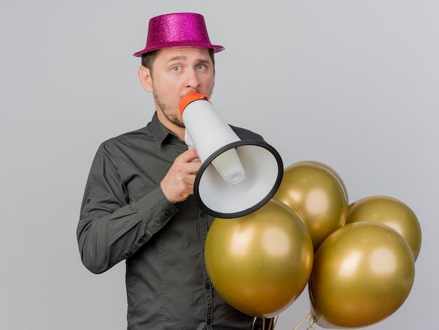 Jeune homme de fête portant un chapeau rose tenant des ballons et parle sur haut-parleur isolé sur blanc