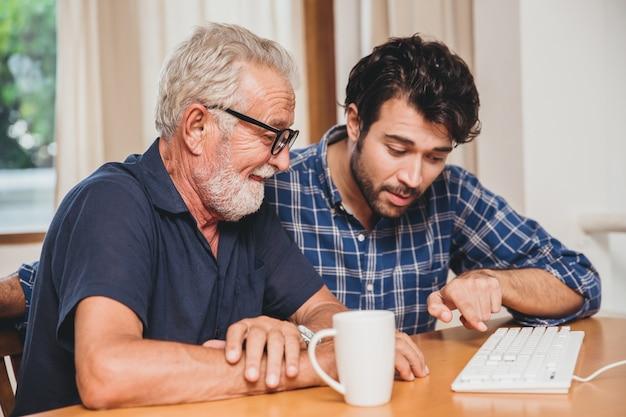 Jeune Homme Ou Fils Enseignant à Son Grand-père Un Père âgé Apprenant à Utiliser Un Ordinateur à La Maison. Photo Premium