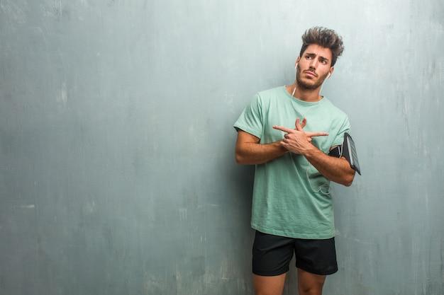 Jeune homme de fitness contre un mur de grunge confus et douteux, décidez entre deux options