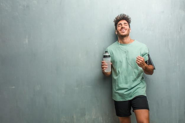 Jeune homme de fitness contre un mur de grunge très heureux et excité, levant les bras