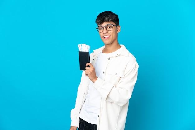 Jeune homme sur fond bleu isolé heureux en vacances avec passeport et billets d'avion