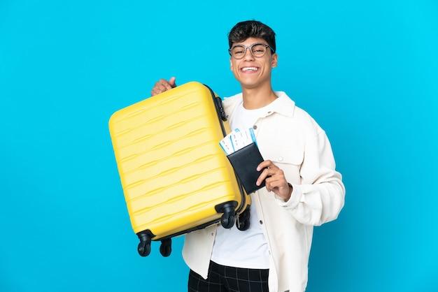 Jeune homme sur fond bleu isolé en vacances avec valise et passeport