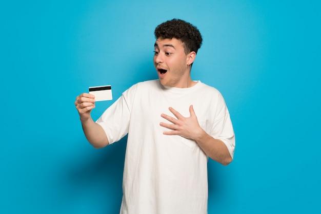 Jeune homme sur fond bleu tenant une carte de crédit et surpris