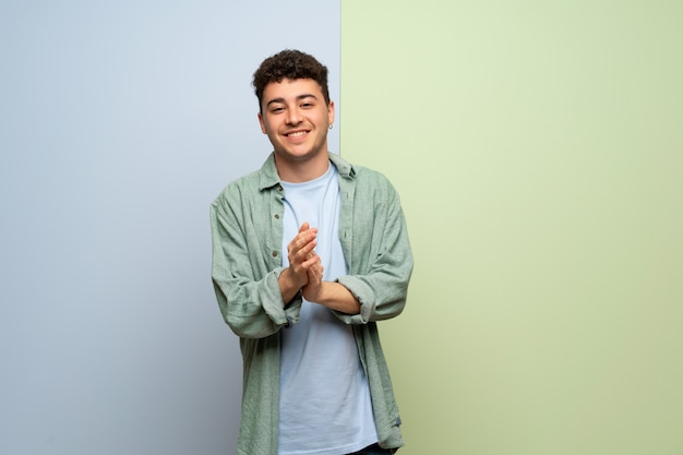 Jeune homme sur fond bleu et vert applaudissant après présentation à une conférence