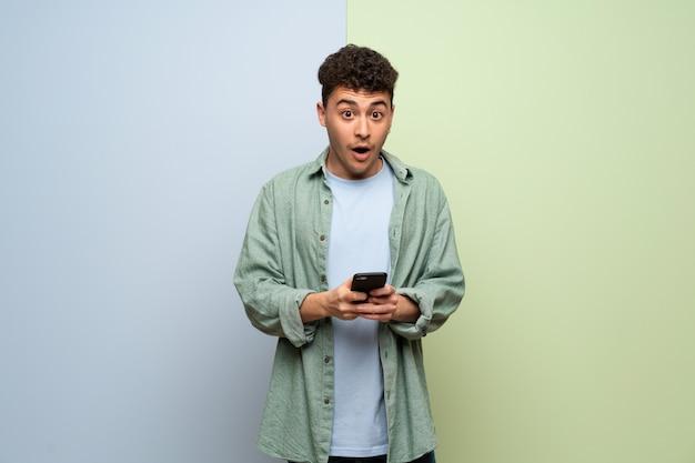 Jeune homme sur fond bleu et vert surpris et envoyant un message