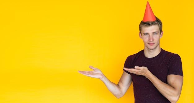 Jeune homme sur fond jaune. concept d'anniversaire avec une casquette sur la tête, pointe avec deux paumes vers un espace vide pour le texte