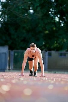 Jeune homme en forme et confiant en position de départ, prêt à courir
