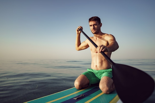 Jeune homme en forme sur paddle board flottant sur le lac au lever du soleil