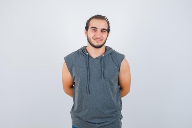 Jeune homme en forme en sweat à capuche sans manches, gardant les mains derrière le dos et regardant gai, vue de face.