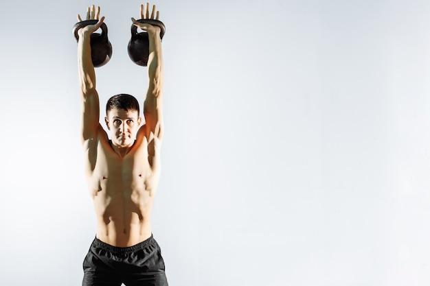 Jeune homme fort exercice avec des haltères sur fond gris