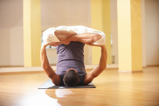 Un jeune homme fort, faire des exercices de yoga. urdhva padmasana inversion lotus pose en studio de yoga