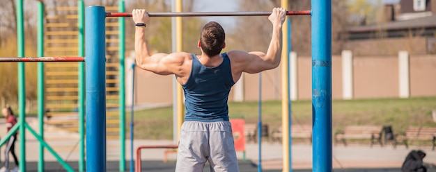 Jeune homme fort se hisse sur la barre horizontale
