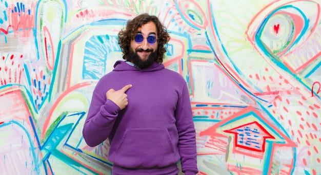 Jeune homme fou barbu à l'air heureux, fier et surpris, pointant gaiement vers lui-même, se sentant confiant et hautain contre un mur de graffitis