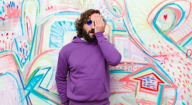 Jeune homme fou barbu ayant l'air endormi, ennuyé et bâillant, avec un mal de tête et une main couvrant la moitié du visage contre un mur de graffitis