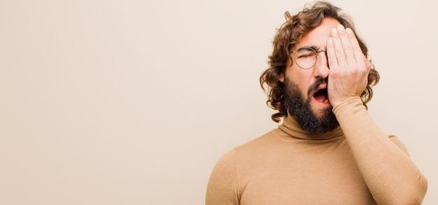 Jeune homme fou barbu ayant l'air endormi, ennuyé et bâillant, avec un mal de tête et une main couvrant la moitié du visage