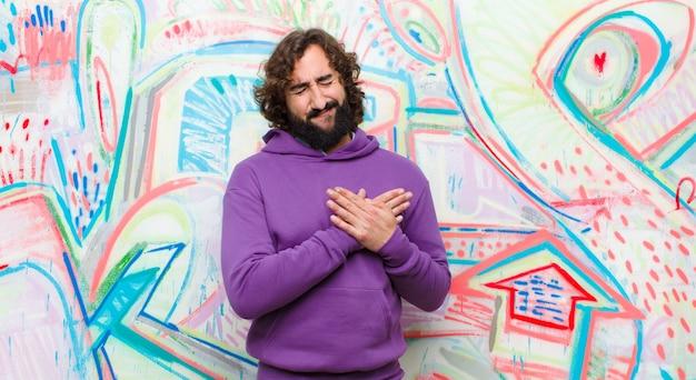 Jeune homme fou barbu ayant l'air triste, blessé et navré, tenant ses deux mains près du cœur, pleurant et se sentant déprimé contre un mur de graffitis