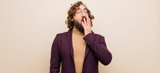 Jeune homme fou barbu bâillant paresseusement tôt le matin, se réveillant et ayant l'air endormi, fatigué et ennuyé contre le mur rose