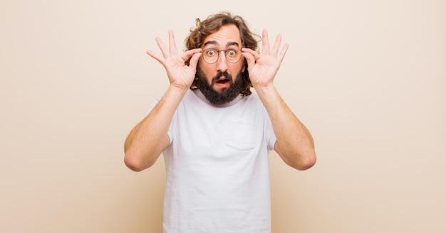 Jeune homme fou barbu, choqué, surpris et surpris, tenant des lunettes avec un regard étonné et incrédule contre le mur rose
