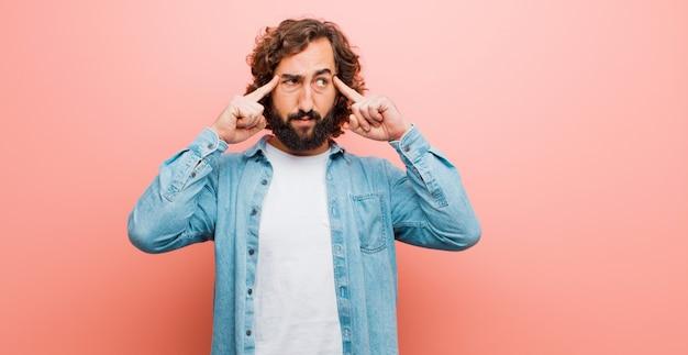 Jeune homme fou barbu, confus ou doutant, se concentrant sur une idée, réfléchissant durement, cherchant à se fondre sur la surface contre une couleur plate
