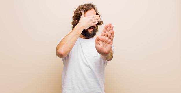 Jeune homme fou barbu couvrant le visage avec la main et mettant l'autre main à l'avant pour arrêter l'appareil photo, refusant les photos ou les images contre la couleur plate