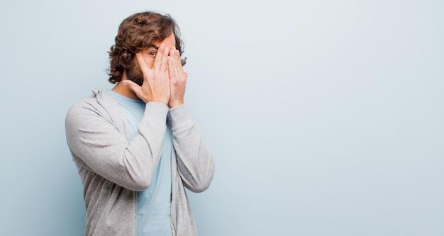 Jeune homme fou barbu couvrant le visage avec les mains, furtivement entre les doigts avec une expression surprise et regardant de côté la couleur plate
