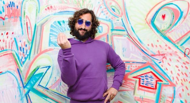 Jeune homme fou barbu faisant capice ou geste d'argent, vous dit de payer vos dettes! contre les graffitis