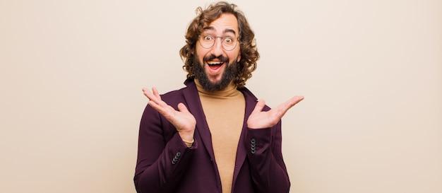 Jeune homme fou barbu, heureux et excité, choqué par une surprise inattendue avec les deux mains ouvertes à côté du visage contre une couleur unie