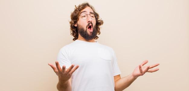 Jeune homme fou barbu jouant de l'opéra ou chantant lors d'un concert ou d'un spectacle, se sentant romantique, artistique et passionné contre la couleur unie