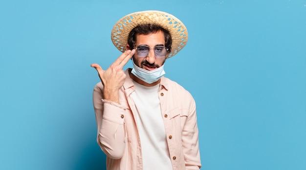 Jeune homme fou barbu avec un masque de covid. concept de voyage.