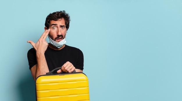 Jeune homme fou barbu avec un masque de protection covid. concept de voyage