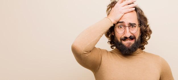 Jeune homme fou barbu paniquant devant une échéance oubliée, se sentant stressé, devant cacher un gâchis ou une erreur contre une couleur unie