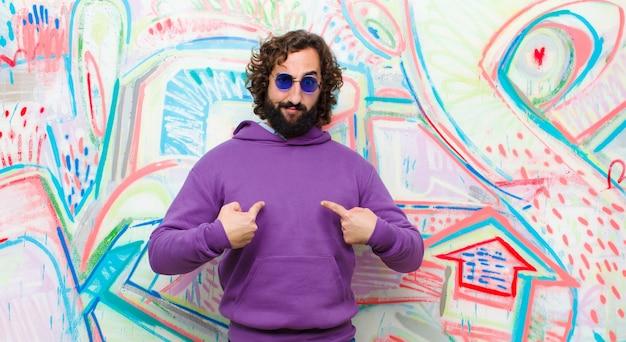 Jeune homme fou barbu pointant sur lui-même avec un regard confus et interrogateur, choqué et surpris d'être choisi contre un mur de graffitis