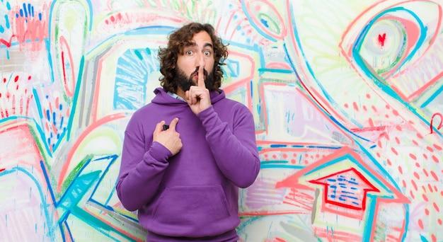 Jeune homme fou barbu à la recherche sérieuse et croix avec le doigt appuyé sur les lèvres exigeant le silence ou la tranquillité, gardant un secret sur le mur de graffitis