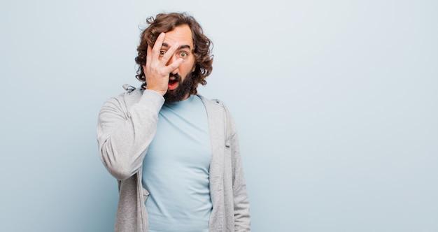 Jeune homme fou barbu regardant choqué, effrayé ou terrifié, couvrant le visage avec la main et furtivement entre les doigts contre le mur de couleur plat