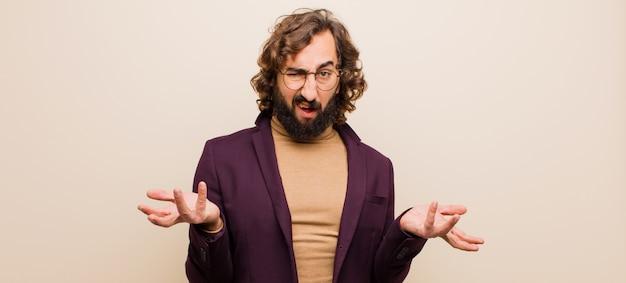 Jeune homme fou barbu se sentant désemparé et confus, ne sachant pas quel choix ou option choisir, se demandant contre un mur plat et coloré