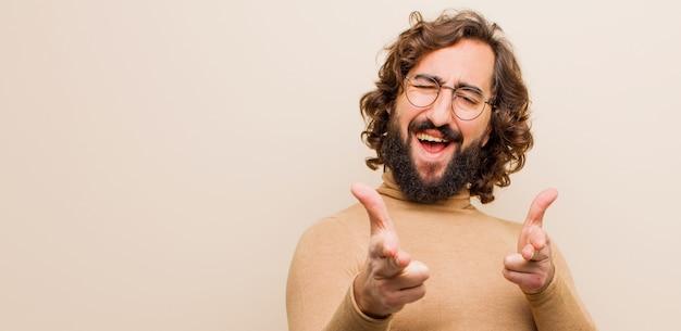 Jeune homme fou barbu se sentant heureux, cool, satisfait, détendu et réussi, pointant, vous choisissant contre une couleur unie
