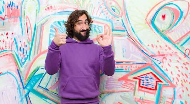 Jeune homme fou barbu se sentir heureux, surpris, satisfait et surpris, montrant bien et gestes, pouce en l'air, souriant sur le mur de graffitis