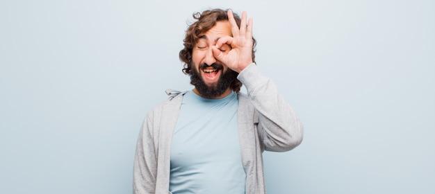 Jeune homme fou barbu souriant joyeusement avec une drôle de tête, plaisantant et regardant à travers un judas, espionnant des secrets contre un mur plat de couleurs