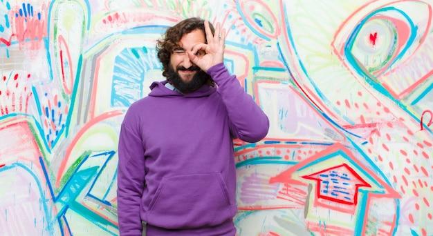 Jeune homme fou barbu souriant joyeusement avec drôle de tête, plaisantant et regardant à travers un judas, espionnant des secrets sur le mur de graffitis