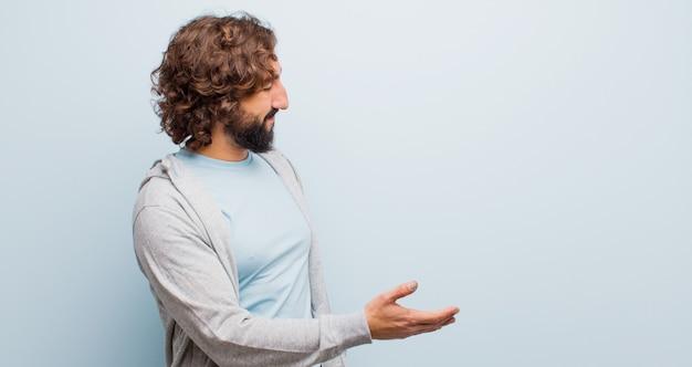 Jeune homme fou barbu souriant, vous saluant et offrant une poignée de main pour conclure un accord fructueux, concept de coopération contre mur couleur plat