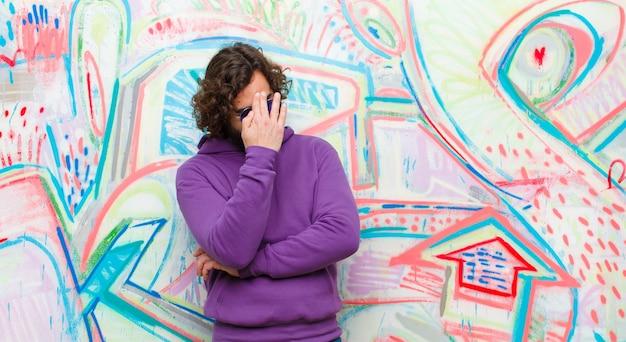 Jeune homme fou barbu, stressé, honteux ou contrarié, souffrant de maux de tête, couvrant le visage de la main contre les graffitis