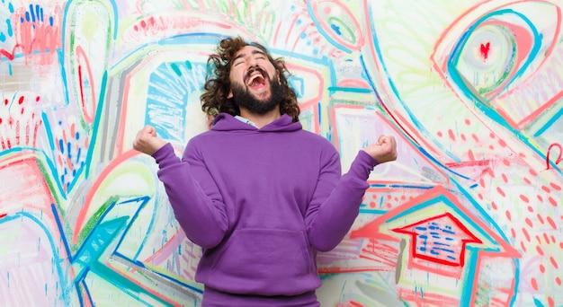 Jeune homme fou barbu très heureux et surpris, célébrant ses succès, criant et sautant contre un mur de graffitis