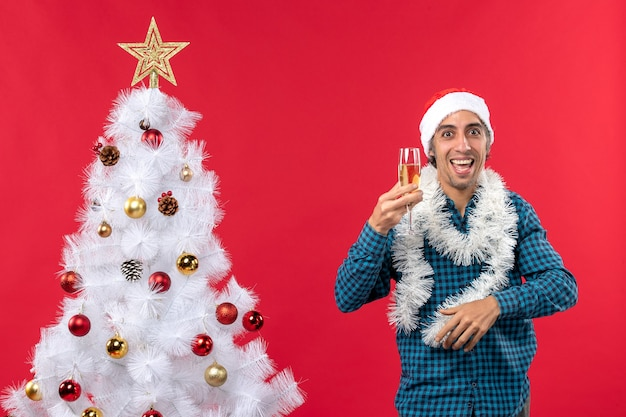 Jeune homme fou avec chapeau de père noël et levant un verre de vin se réjouit près de l'arbre de noël
